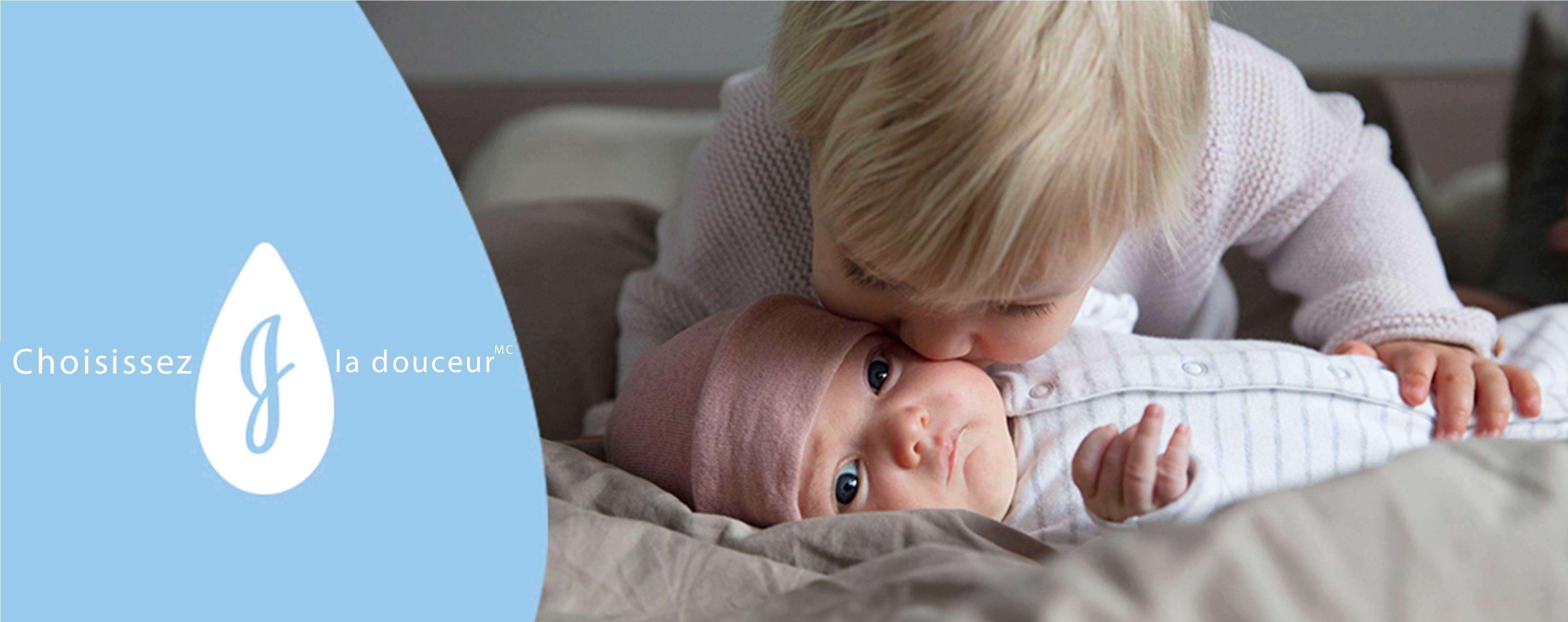 Un enfant embrassant la joue douce d'un bébé allongé sur un lit