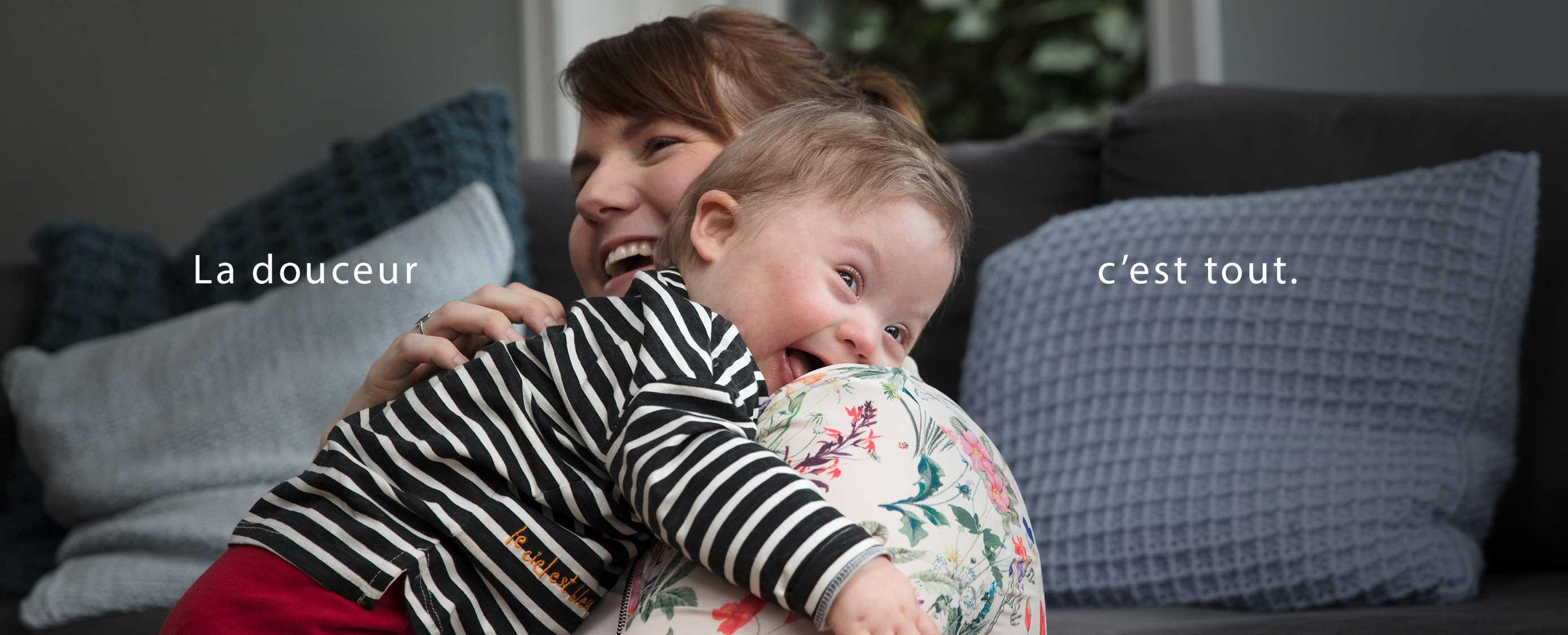 Une maman prenant un bébé souriant dans ses bras