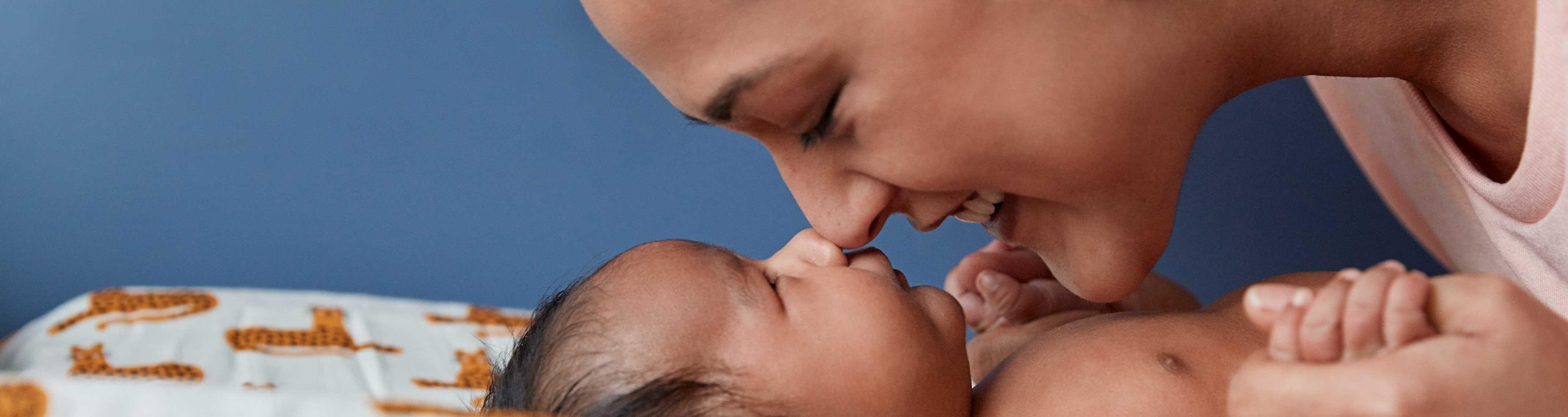 Une maman et un nouveau-né qui se touchent le nez, allongés sur un lit