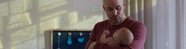 Un papa mettant son bébé au lit