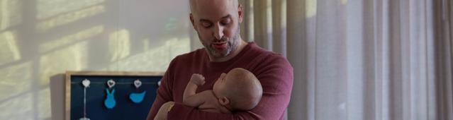 Un papa berçant son bébé pour l'endormir