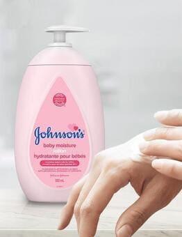 Lotion pour bébés JOHNSON'S® appliquée sur la main d'une adulte