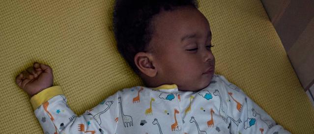 Un bébé endormi dans un berceau en bois