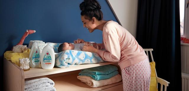 Une maman et un bébé dans une chambre de bébé avec des produits pour bébés Johnson's®