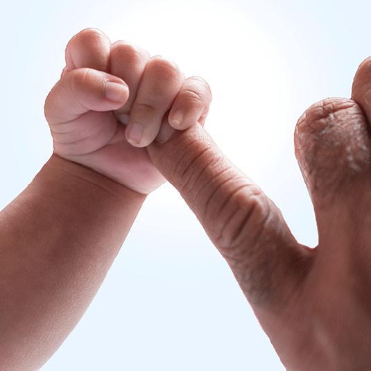 Une main de bébé tenant le doigt d'un adulte