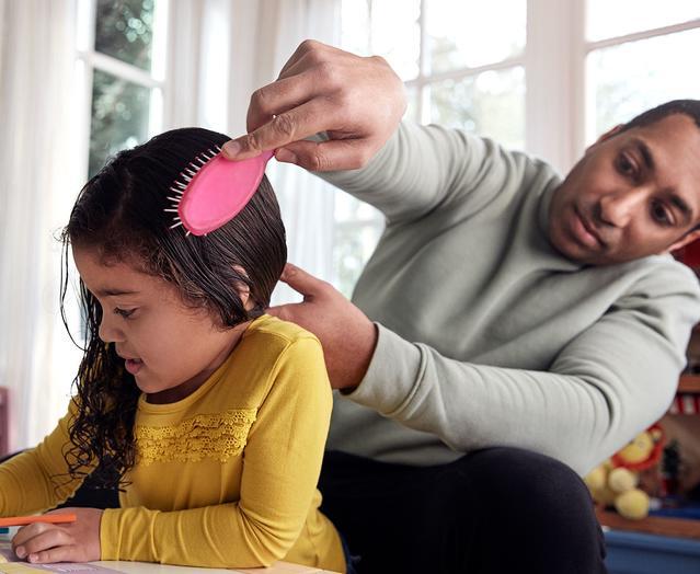 Un papa peignant les cheveux de son enfant