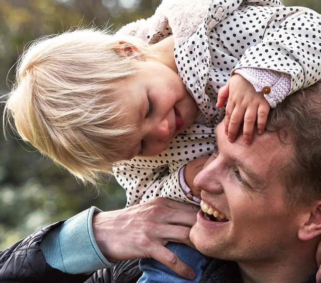 Un bébé et un papa qui jouent dehors