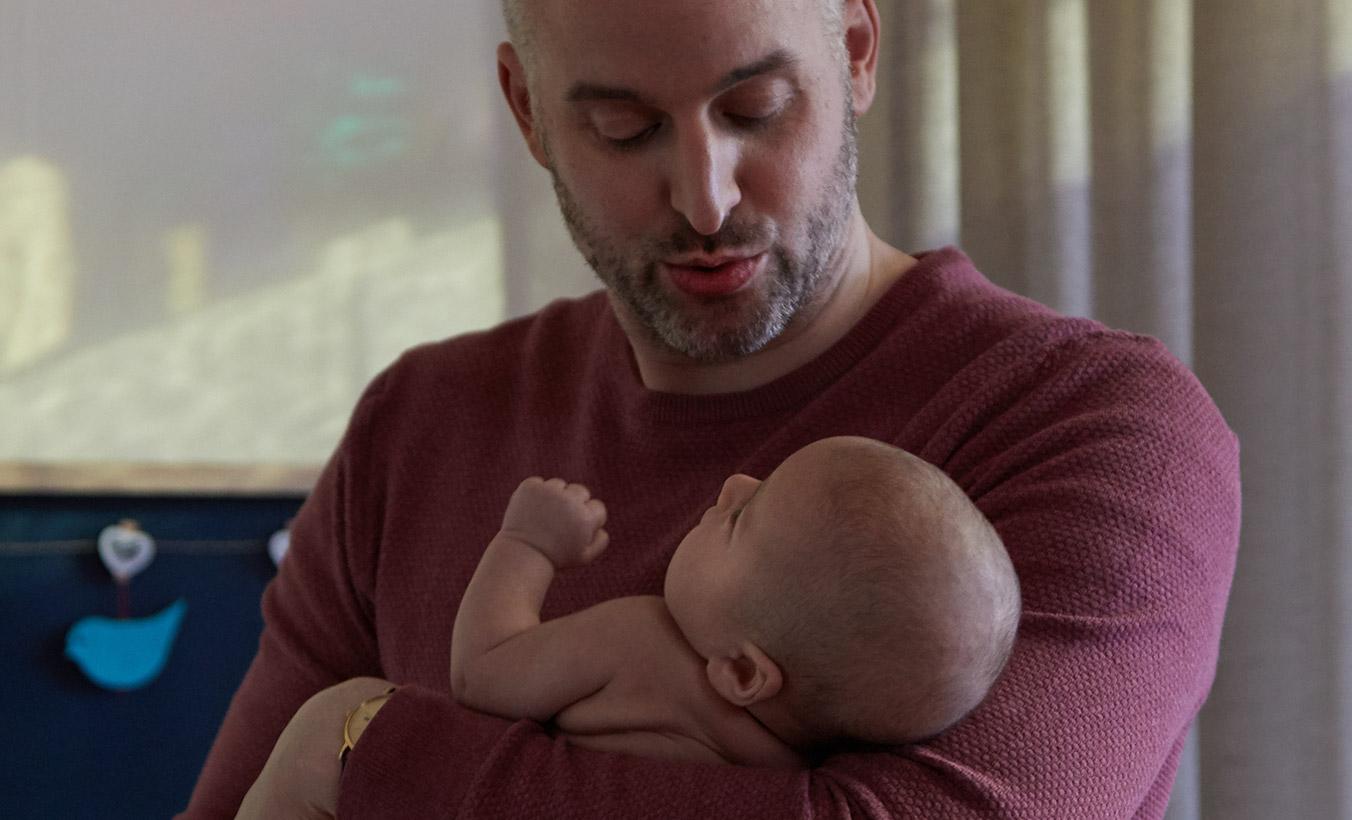 Un papa mettant au lit son nouveau-né