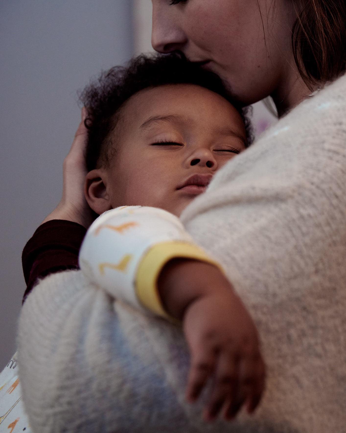 Une maman embrassant et tenant dans ses bras un bébé endormi