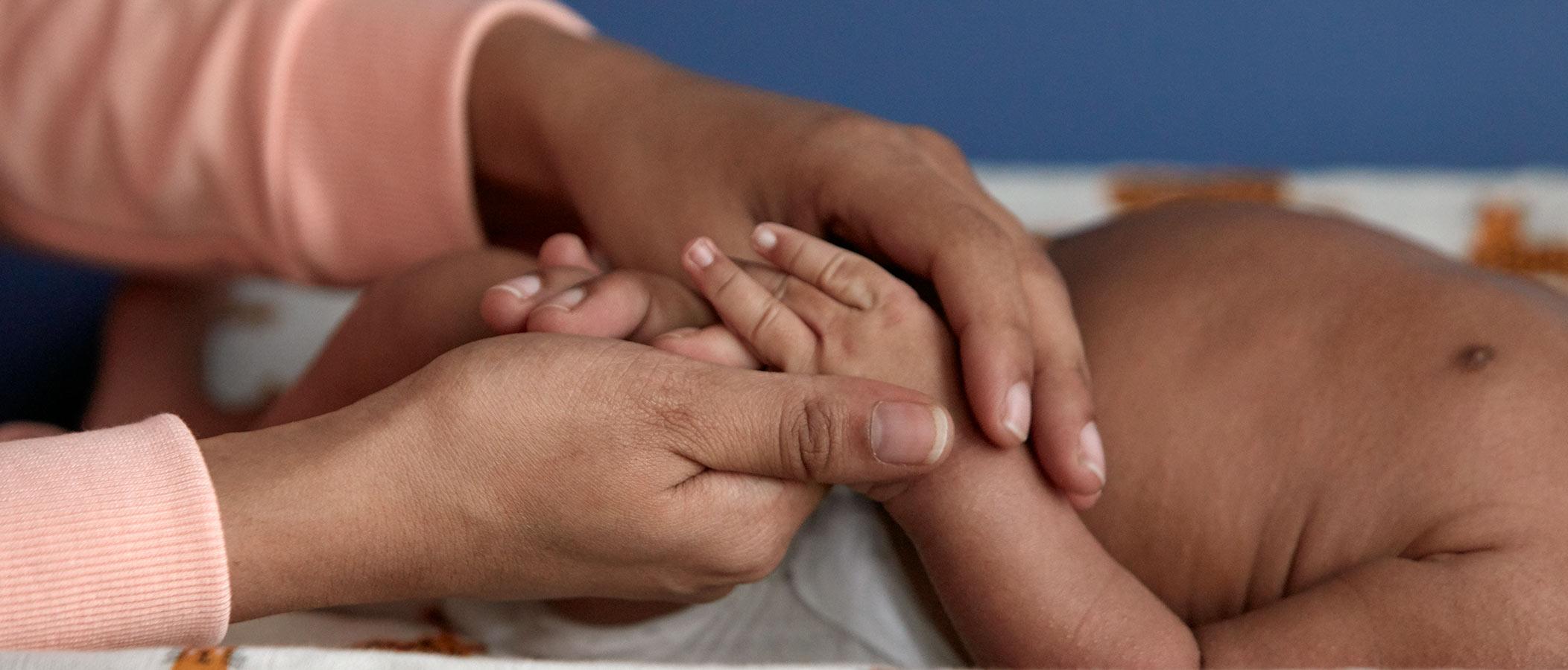 Un nouveau-né se faisant masser la main