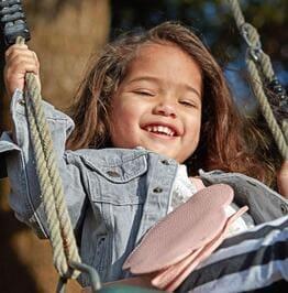 Un bambin souriant, assis sur une balançoire